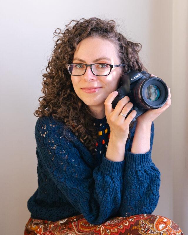 Ewa Kara, London photographer, sitting, holding camera and smiling